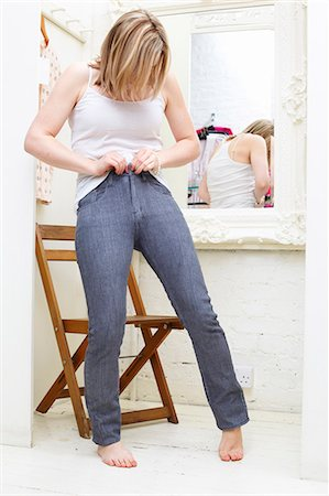 Woman trying on jeans Stock Photo - Premium Royalty-Free, Code: 649-03817681