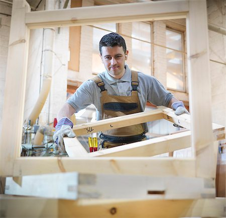 Woodworker with window frames Stock Photo - Premium Royalty-Free, Code: 649-03817812