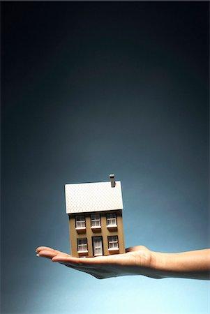 Ladies hand holding model house Stock Photo - Premium Royalty-Free, Code: 649-03818004
