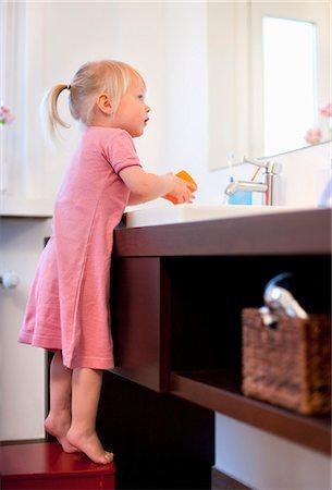 Toddler girl washing her hands Stock Photo - Premium Royalty-Free, Code: 649-03857841