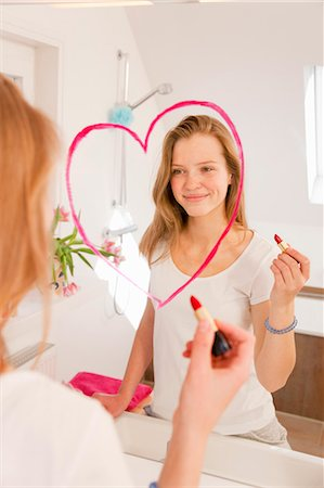 Teenage girl drawing heart in lipstick Stock Photo - Premium Royalty-Free, Code: 649-03857864