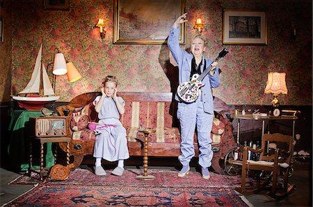 Older woman playing guitar as girl knits Stock Photo - Premium Royalty-Free, Code: 649-03858056