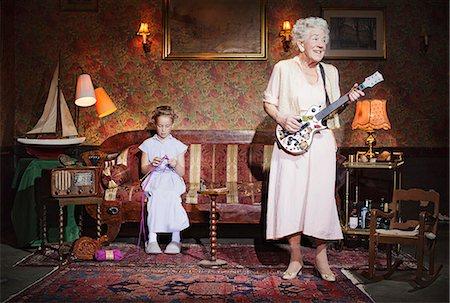 Older woman playing guitar as girl knits Stock Photo - Premium Royalty-Free, Code: 649-03858051