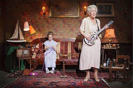 Older woman playing guitar as girl knits Stock Photo - Premium Royalty-Free, Code: 649-03858052