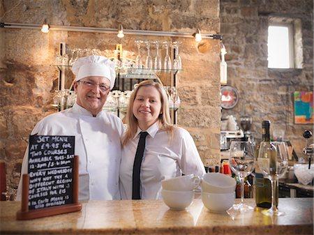 Chef and waitress standing behind bar Stock Photo - Premium Royalty-Free, Code: 649-03858169