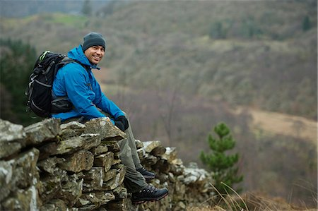 Hiking man sitting on stone wall Stock Photo - Premium Royalty-Free, Code: 649-03858414