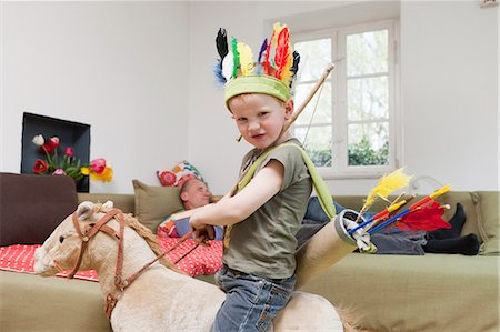 Boy in war bonnet playing with toys Stock Photo - Premium Royalty-Free, Code: 649-03884188