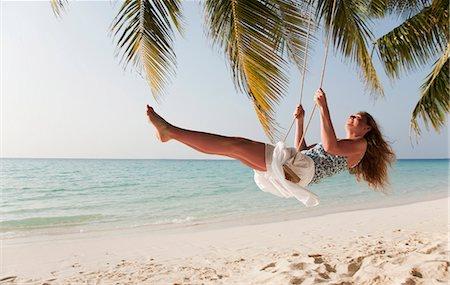 Smiling woman swinging on tropical beach Stock Photo - Premium Royalty-Free, Code: 649-03881283