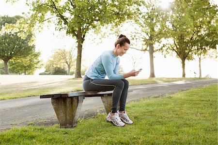 people sitting on bench - Runner using cell phone in park Stock Photo - Premium Royalty-Free, Code: 649-03881909