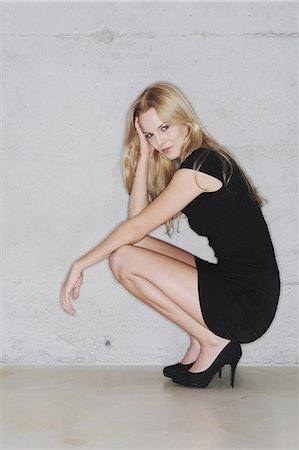 Woman crouching in short black dress Stock Photo - Premium Royalty-Free, Code: 649-03883202