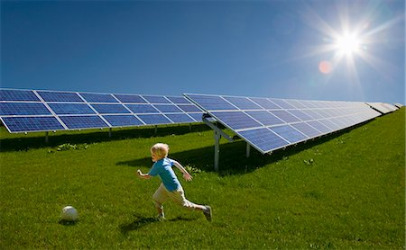 energia alternativa - Boy playing in field by solar panels Foto de stock - Royalty Free Premium, Número: 649-03883516