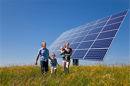 solar power - Family walking in field by solar panel Stock Photo - Premium Royalty-Free, Code: 649-03883521
