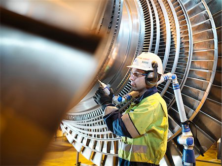 Worker inspects turbine in power station Stock Photo - Premium Royalty-Free, Code: 649-03883728