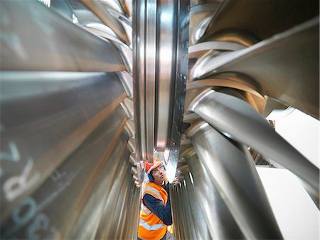 Worker inspects turbine in power station Stock Photo - Premium Royalty-Free, Code: 649-03883738