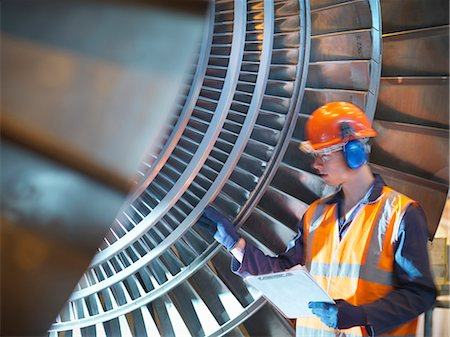 Worker inspects turbine in power station Stock Photo - Premium Royalty-Free, Code: 649-03883732