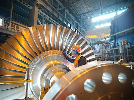 Worker inspects turbine in power station Stock Photo - Premium Royalty-Free, Code: 649-03883741