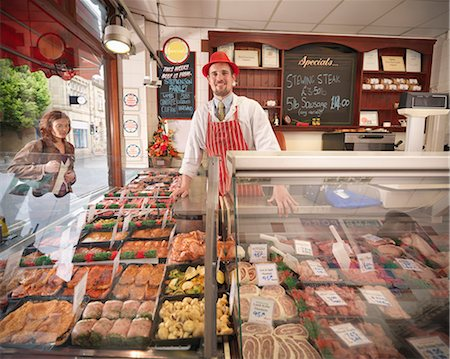 Butcher standing behind counter in shop Stock Photo - Premium Royalty-Free, Code: 649-03883825