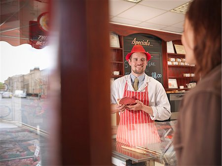 Butcher showing meat to customer Stock Photo - Premium Royalty-Free, Code: 649-03883826