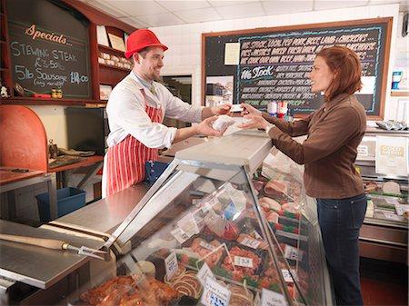 Butcher handing meat to customer Stock Photo - Premium Royalty-Free, Code: 649-03883828