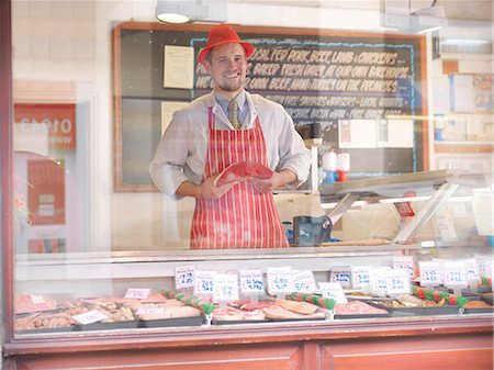 Butcher holding steak behind counter Stock Photo - Premium Royalty-Free, Code: 649-03883829
