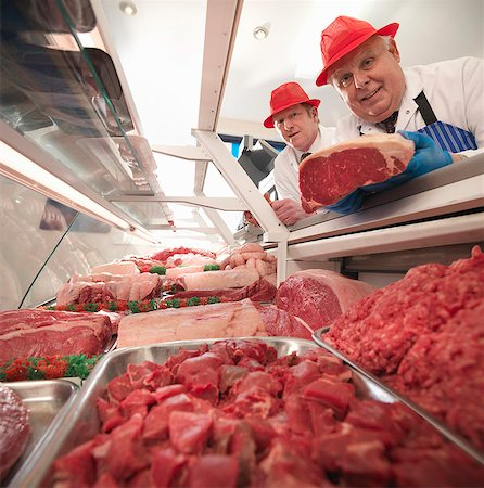Butcher examining meat in case Stock Photo - Premium Royalty-Free, Code: 649-03883834