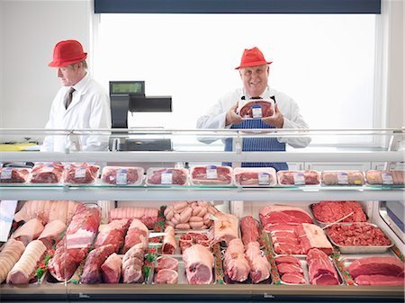 Butcher standing behind meat counter Stock Photo - Premium Royalty-Free, Code: 649-03883831