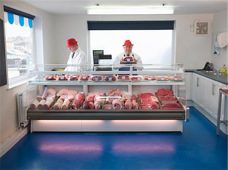 Butcher standing behind meat counter Stock Photo - Premium Royalty-Free, Code: 649-03883832