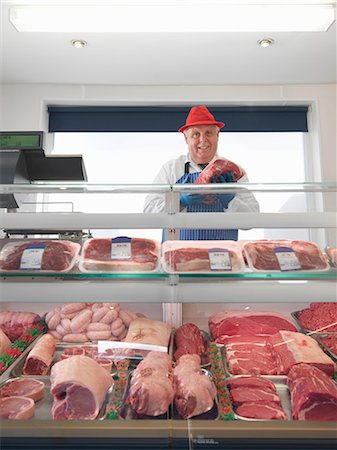 Butcher standing behind meat counter Stock Photo - Premium Royalty-Free, Code: 649-03883833