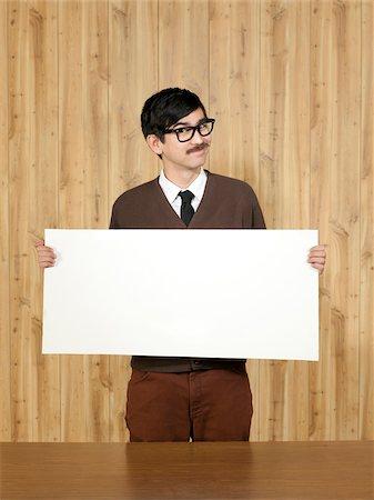 filipino (male) - Studio portrait of businessman holding blank placard Stock Photo - Premium Royalty-Free, Code: 640-05761196