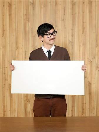 filipino (male) - Studio portrait of businessman holding blank placard Stock Photo - Premium Royalty-Free, Code: 640-05761196