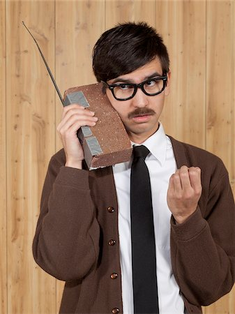 filipino (male) - Businessman using brick mobile phone in office Stock Photo - Premium Royalty-Free, Code: 640-05761193