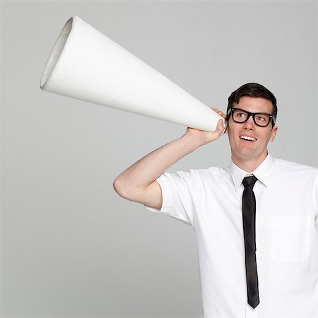 Studio portrait of young man with megaphone Stock Photo - Premium Royalty-Free, Code: 640-05761229