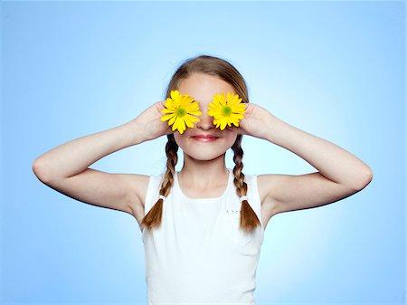 preteen girl - Studio portrait of girl (10-11) shielding eyes by two yellow flowers Stock Photo - Premium Royalty-Free, Code: 640-05761259