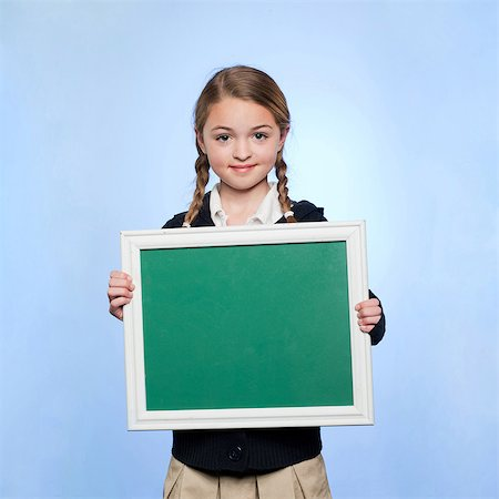 showing - Studio portrait of girl (10-11) holding blank green chalkboard Stock Photo - Premium Royalty-Free, Code: 640-05761274