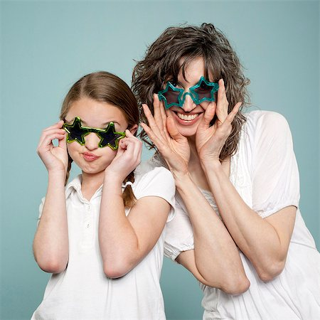 preteen touch - Studio shot of mother and daughter (10-11) wearing star shaped sunglasses Stock Photo - Premium Royalty-Free, Code: 640-05761279