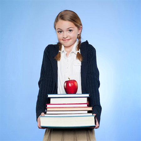 school girl uniforms - Studio portrait of girl (10-11) holding stack of books and apple Stock Photo - Premium Royalty-Free, Code: 640-05761270