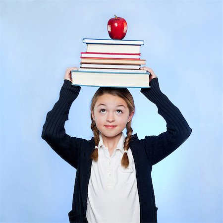 school girl uniforms - Studio shot of girl (10-11) holding stack of books and apple on head Stock Photo - Premium Royalty-Free, Code: 640-05761271