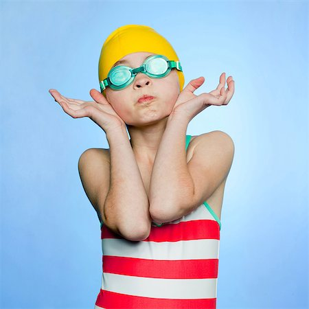 Studio shot of girl (10-11) wearing swimsuit, swimming cap and swimming goggles Stock Photo - Premium Royalty-Free, Code: 640-05761289