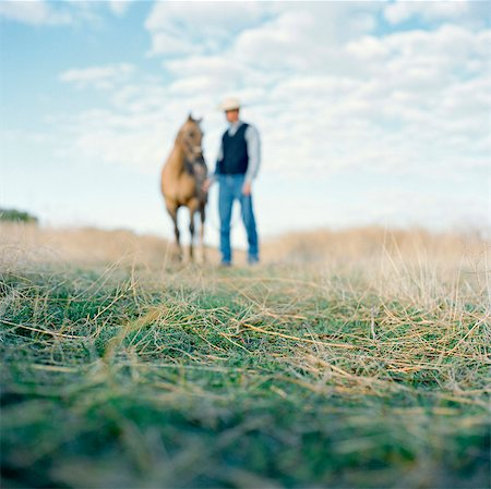 USA, Utah, Mapleton, Cowboy standing with horse at pasture, focus on grass Stock Photo - Premium Royalty-Free, Code: 640-05761380
