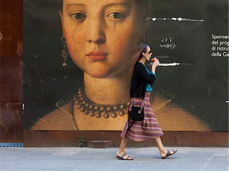 poster - Italy, Florence, Young woman walking past portrait in city Stock Photo - Premium Royalty-Free, Code: 640-06049925