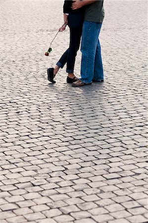 Italy, Rome, Vatican City, Close up of legs of couple with rose standing on cobblestone Stock Photo - Premium Royalty-Free, Code: 640-06050025