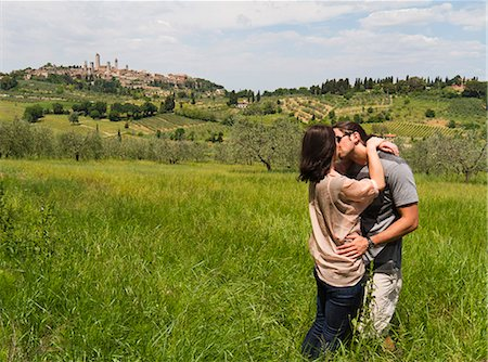 romance - Italy, Tuscany, San Gimignano, Young couple kissing on meadow Stock Photo - Premium Royalty-Free, Code: 640-06050323