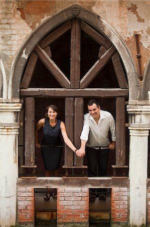 Italy, Venice, Couple standing in arcade Stock Photo - Premium Royalty-Free, Code: 640-06050333