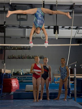 preteen girls stretching - USA, Utah, Orem, girls (10-11) in gym watching friend exercising on pole Stock Photo - Premium Royalty-Free, Code: 640-06050734