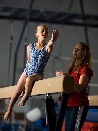 preteen girls stretching - USA, Utah, Orem, girl (10-11) exercising on balance beam with teacher Stock Photo - Premium Royalty-Free, Code: 640-06050738