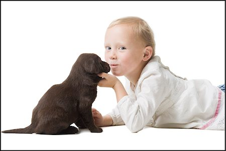 dog kissing girl - child with puppy Stock Photo - Premium Royalty-Free, Code: 640-06050845