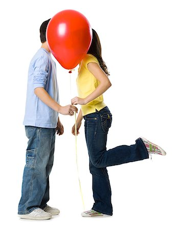 preteen kissing - couple kissing behind a red balloon Stock Photo - Premium Royalty-Free, Code: 640-06051396