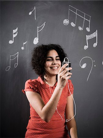 woman listening to mp3 player Stock Photo - Premium Royalty-Free, Code: 640-06052038