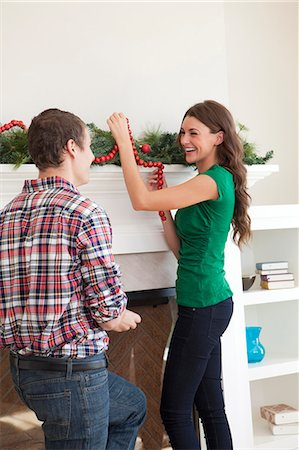 Smiling couple decorating room for Christmas Stock Photo - Premium Royalty-Free, Code: 640-06963399