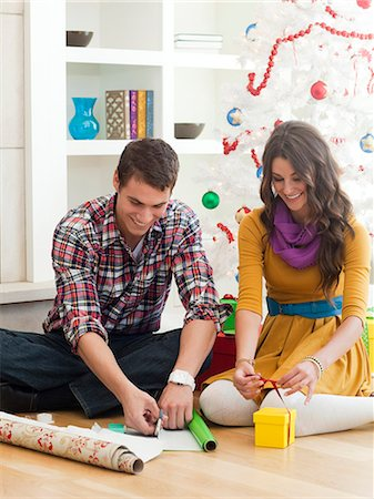 Young couple sitting under Christmas tree, wrapping Christmas presents Stock Photo - Premium Royalty-Free, Code: 640-06963425